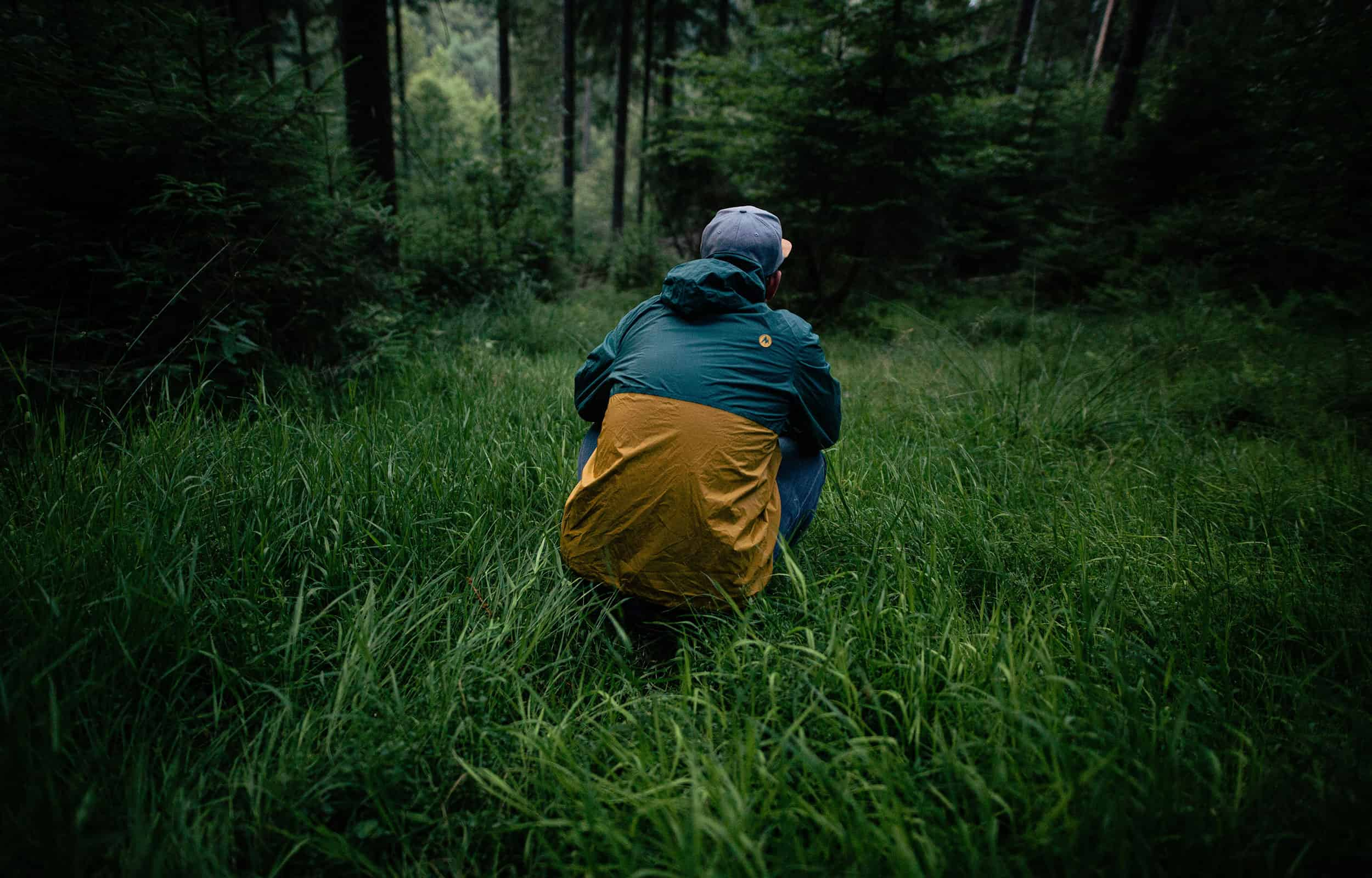guy squatting in a wooded area wearing a rain jacket