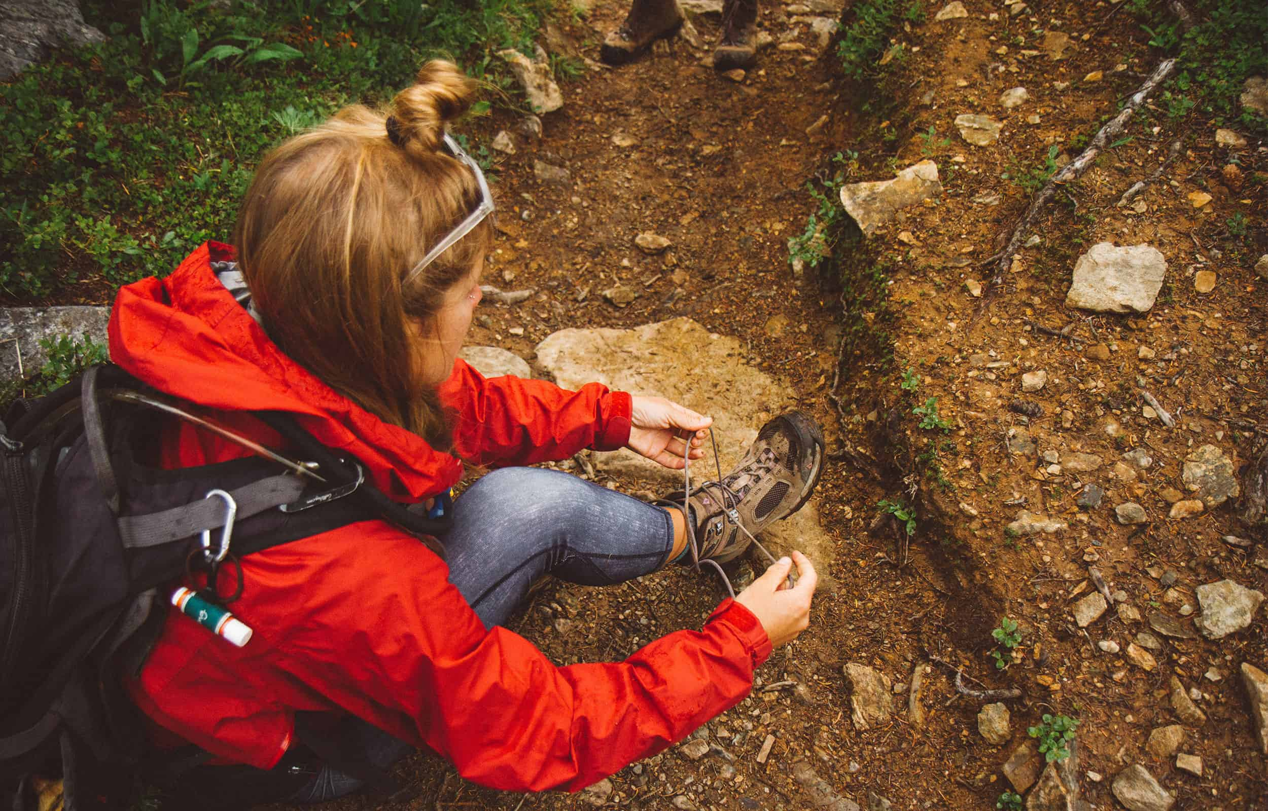 hiker tying her boots wearing a red hardshell jacket
