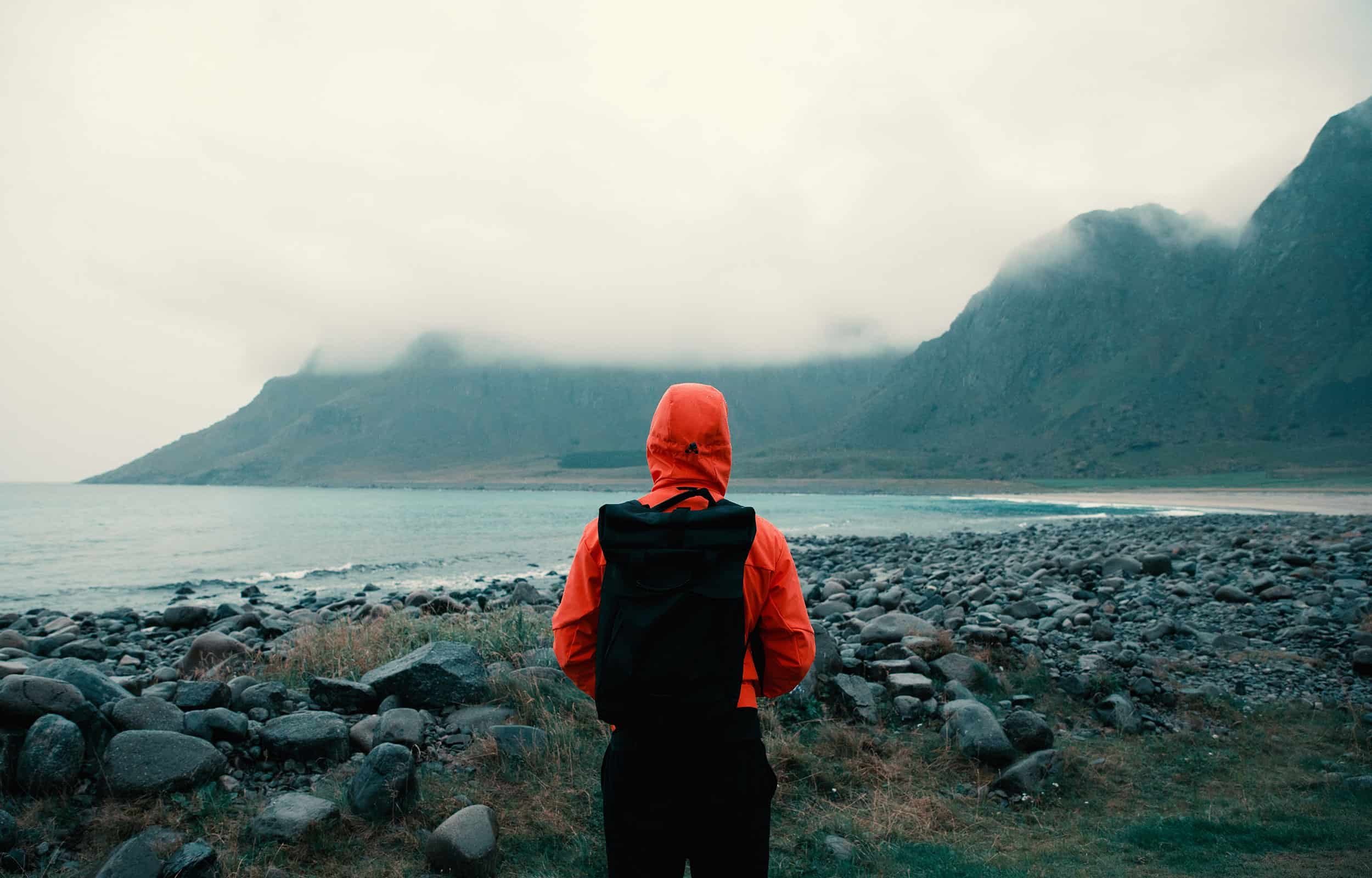person looking at a lake and mountain in misty weather