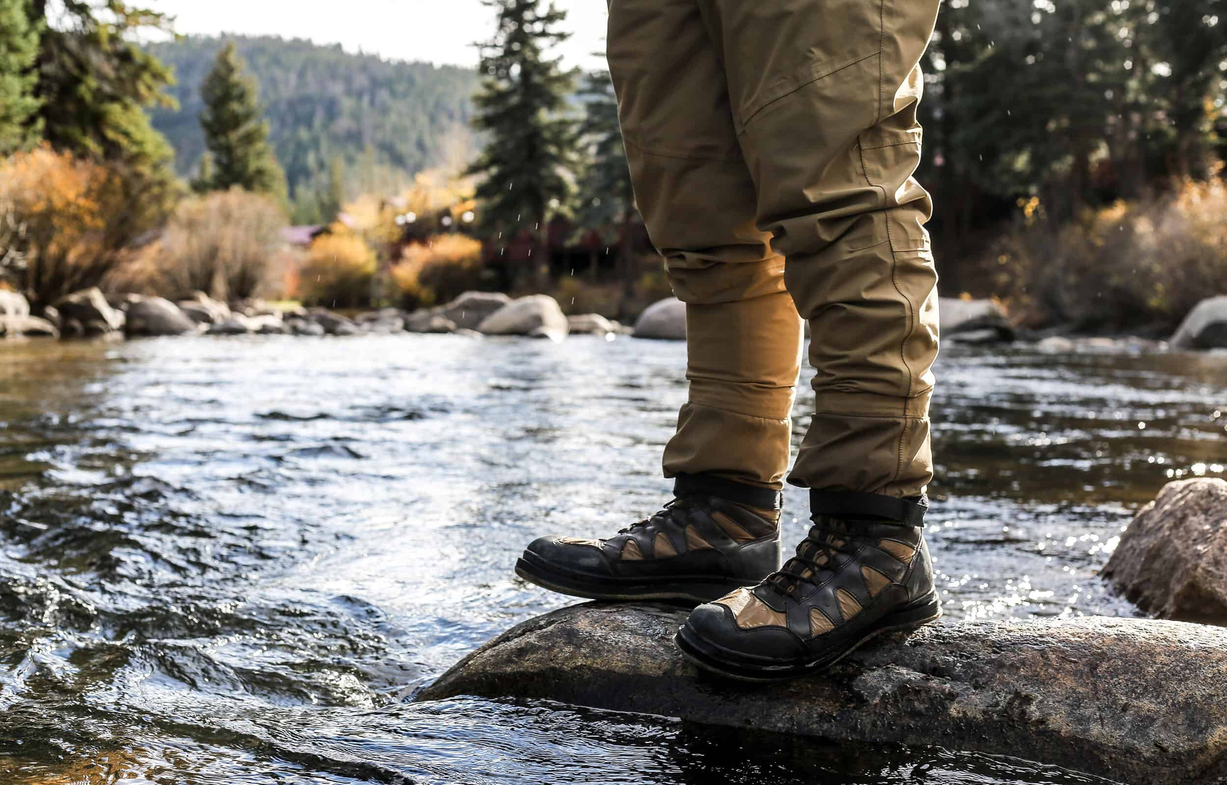 hiking boots standing on rocks in a river