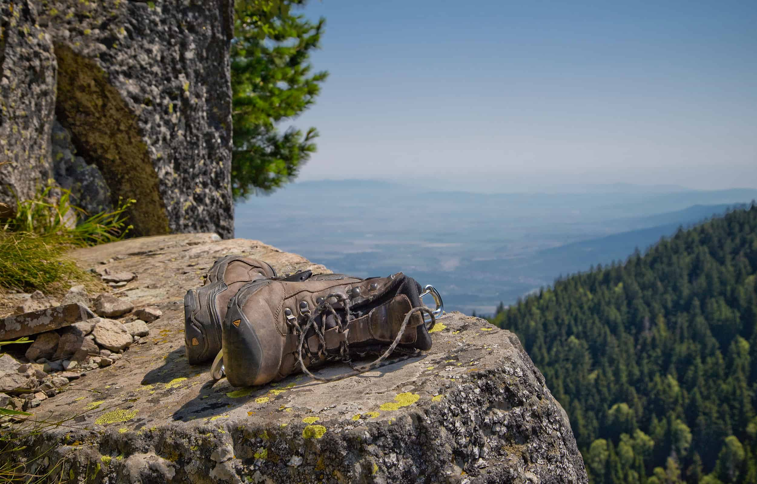 a pair of hiking boots laying on a rock ledge