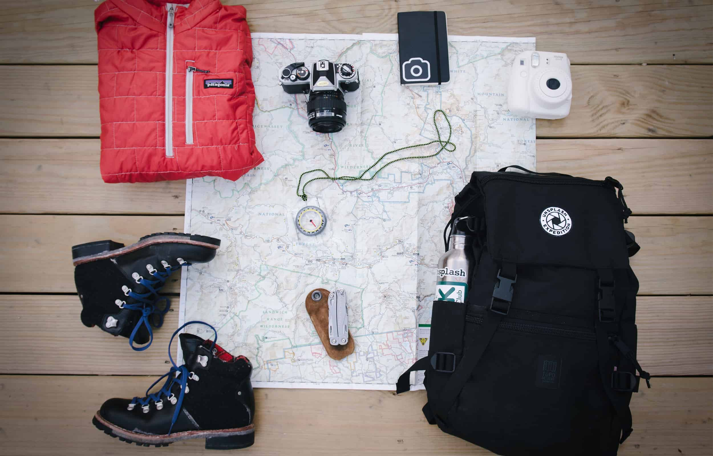 hiking gears pf backpack, camera, hiing boots, hiking jacket, compass, and a map
