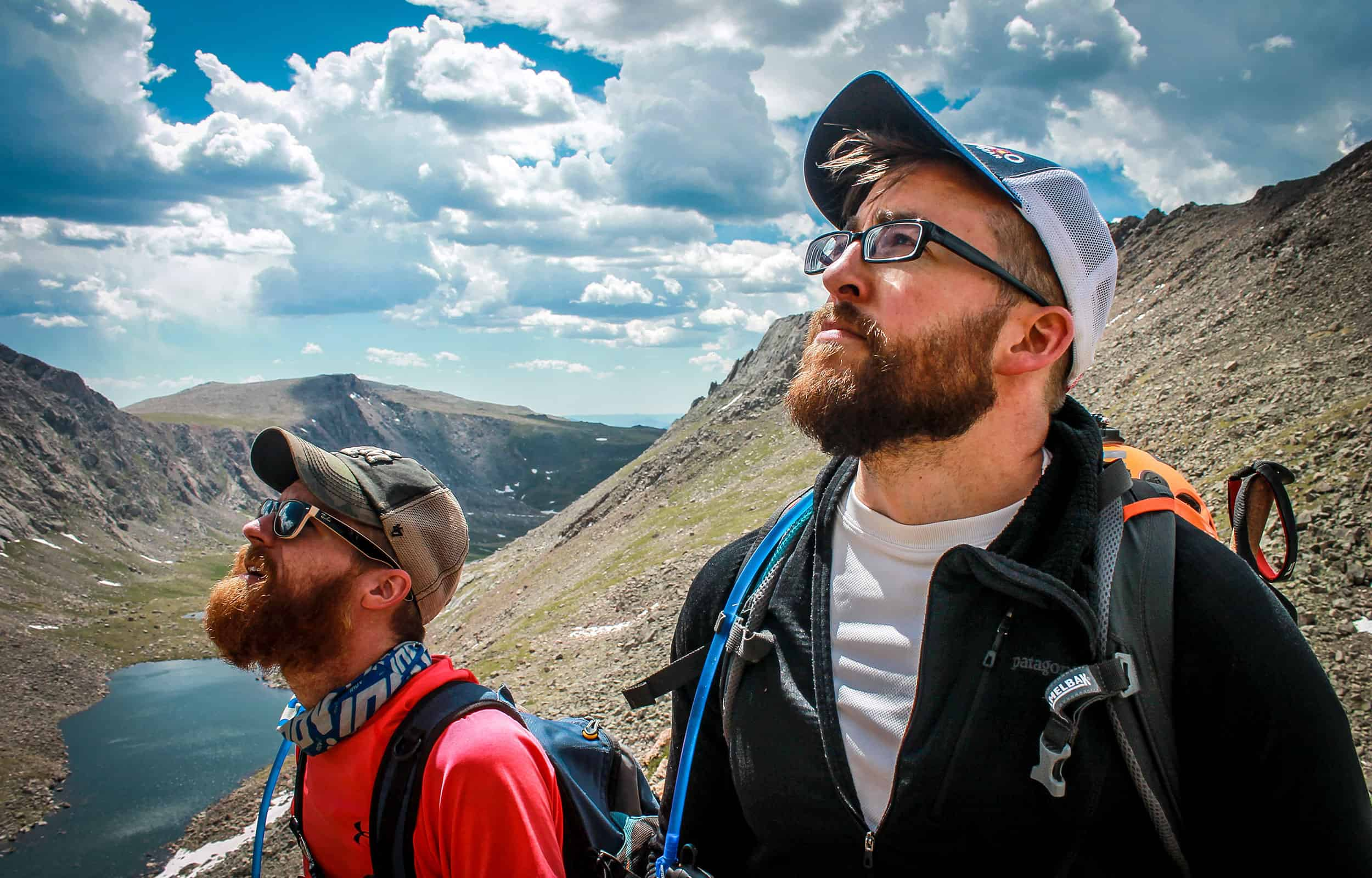 two guys looking at the sky while hiking determining what is up ahead