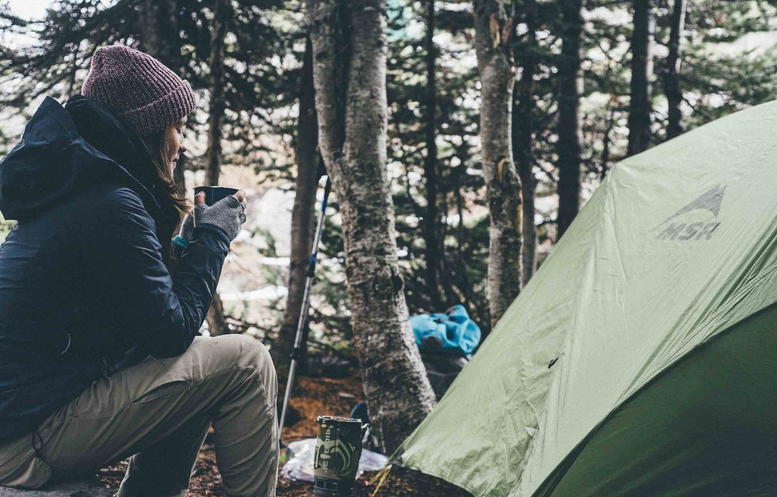 woman sitting by her camping tent to repair
