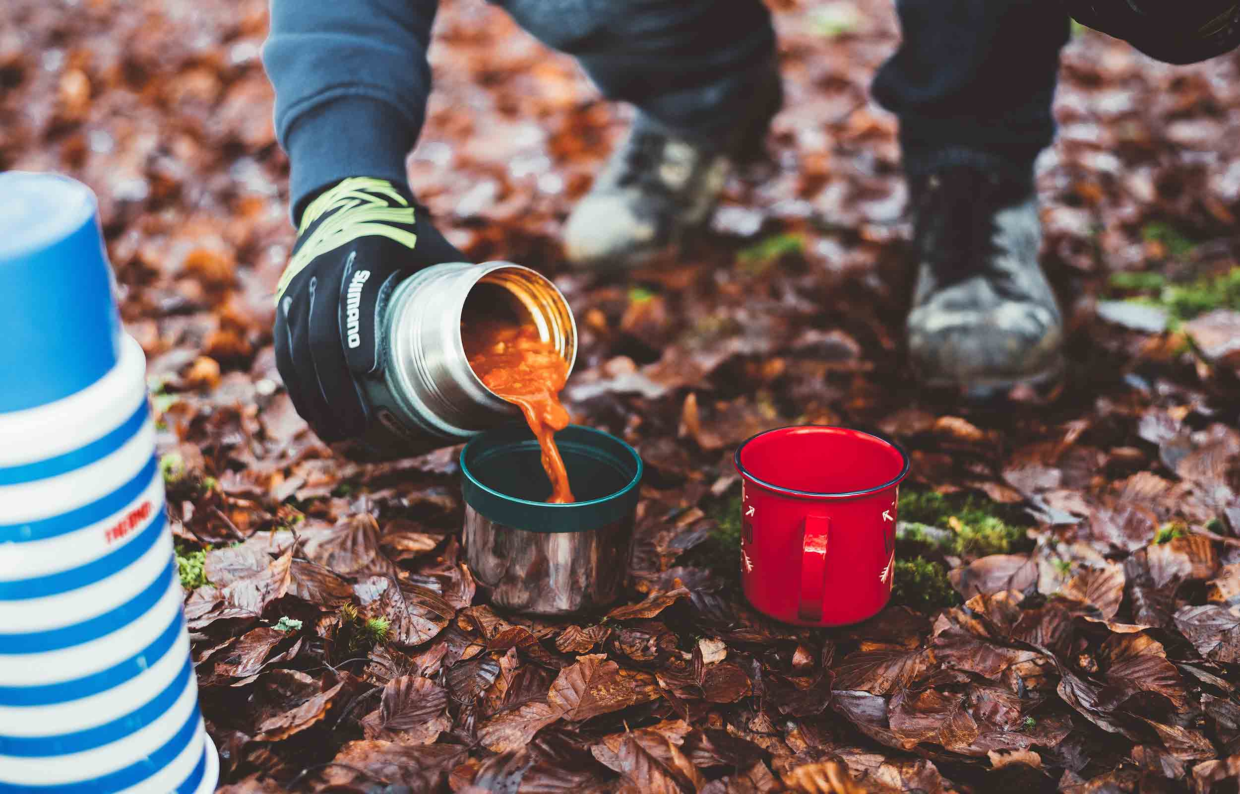 hiker pouring hot soup into a cup