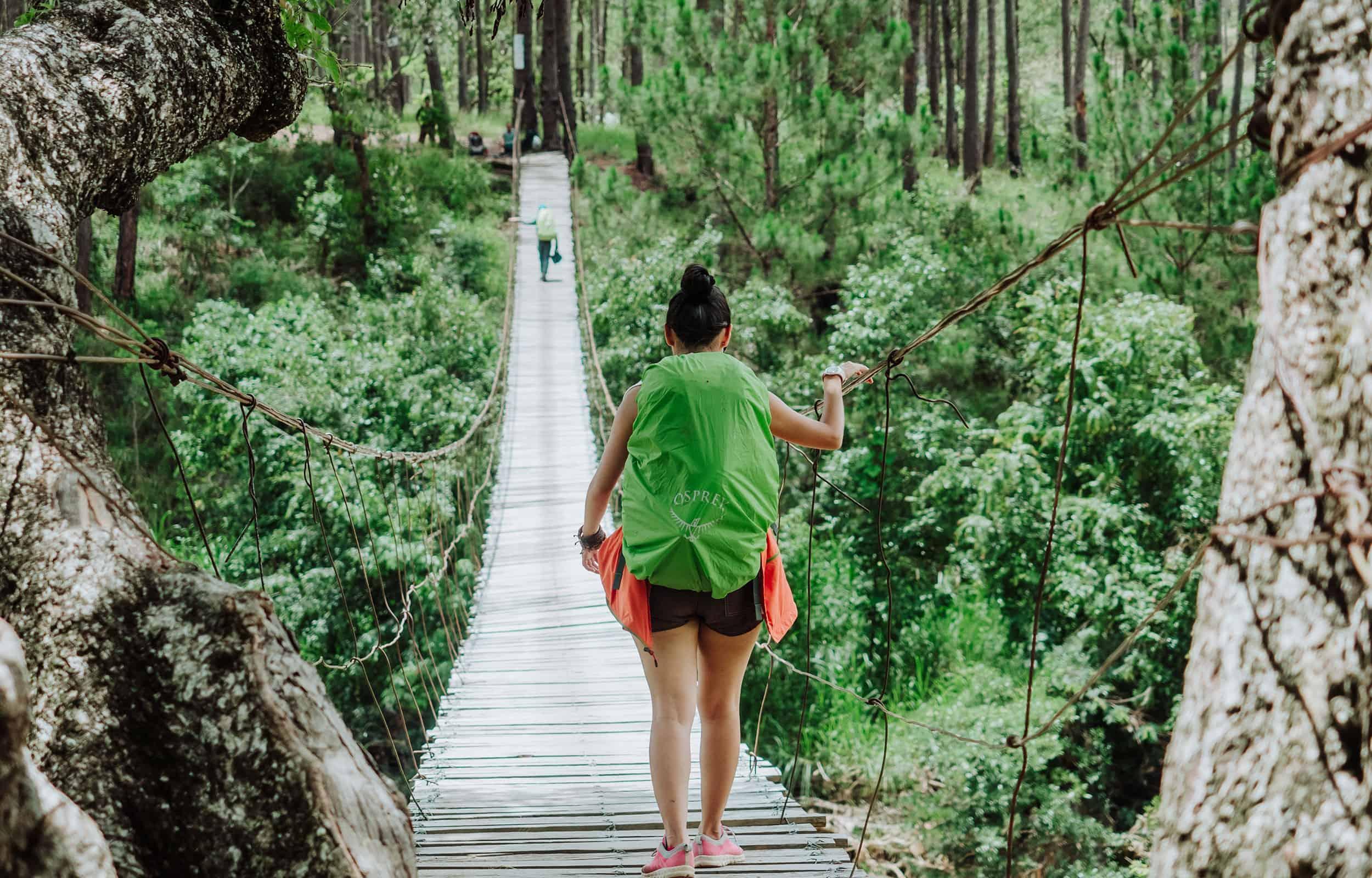 woman crossing a suspended bridge